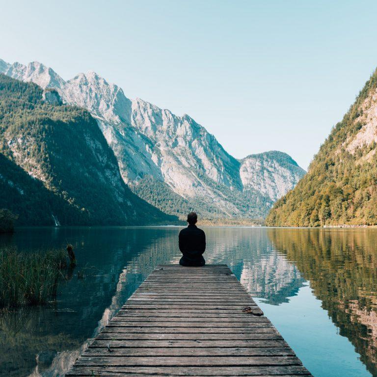 Kuvassa näkyy henkilö takaapäin istumassa sillan päässä katsomassa vuorimaisemassa.