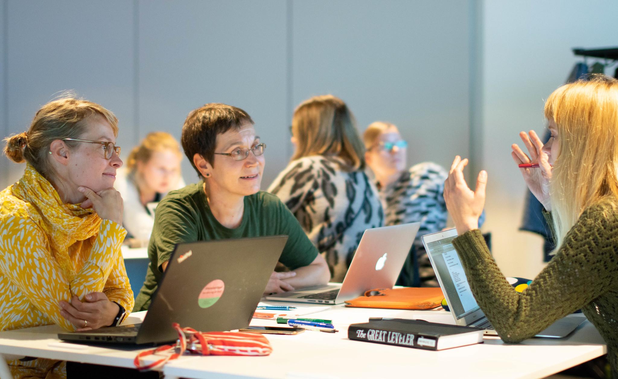 Opettajat keskustelevat koulutustilaisuudessa istuessaan pöydän ympärillä.