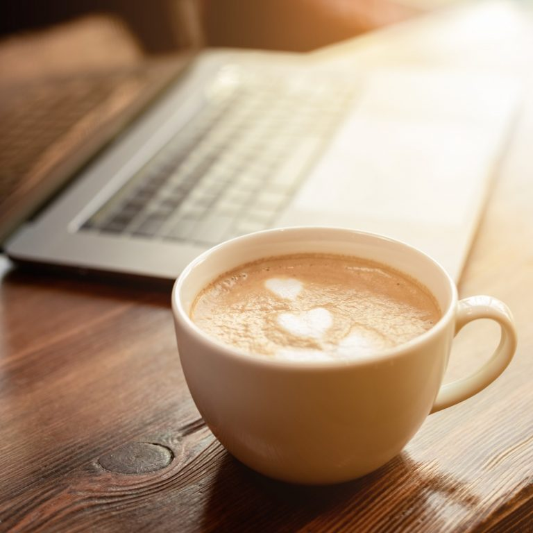 Kahvikuppi puisella pöydällä. Takana kannettava tietokone.