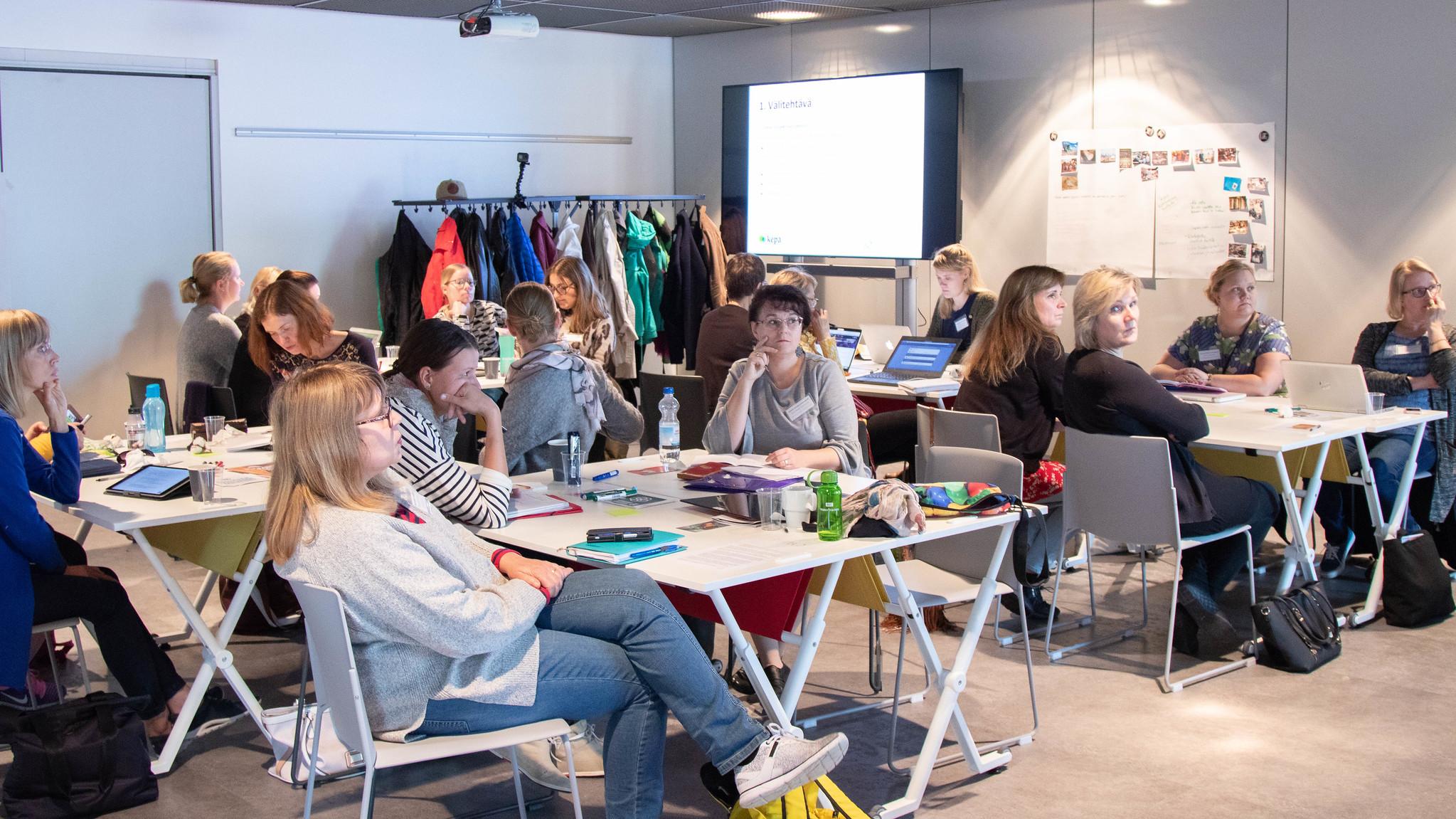 Opettajia istumassa kokoushuoneessa koulutuksessa.