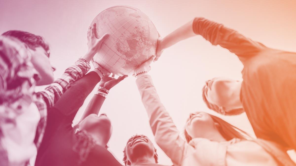 Viisi ihmistä seisoo ringissä ja pitelee käsissään maapalloa.