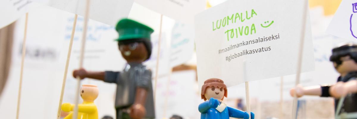 Legomielenosoitus, jonka yhdessä kyltissä teksti: Luomalla toivoa #maailmankansalaiseksi #globaalikasvatus.