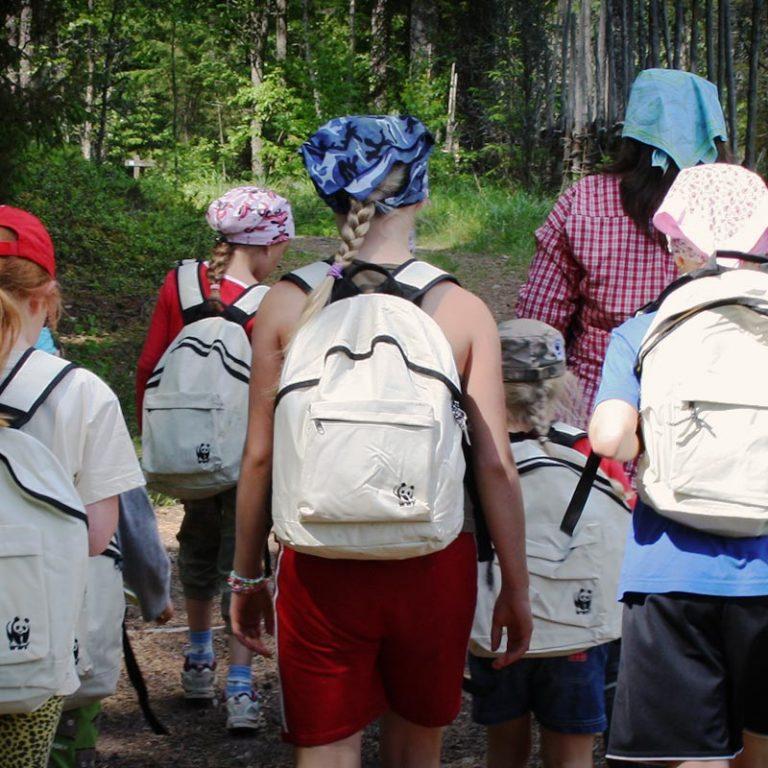 Kuvassa lapsia reput selässä selin kameraan