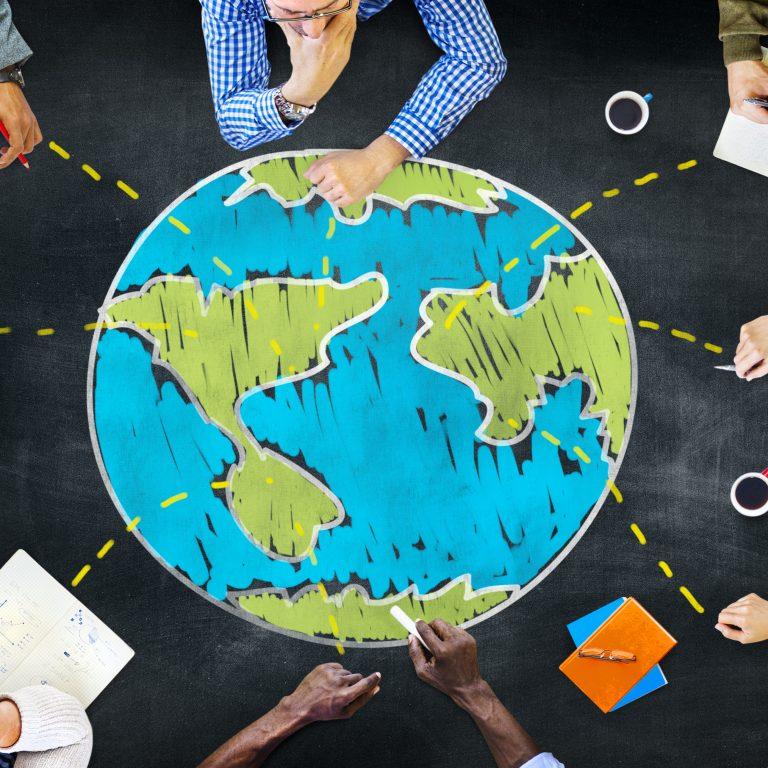 Ihmiset istuvat pöydän äärellä, mihin piirretty kuva maapallosta.